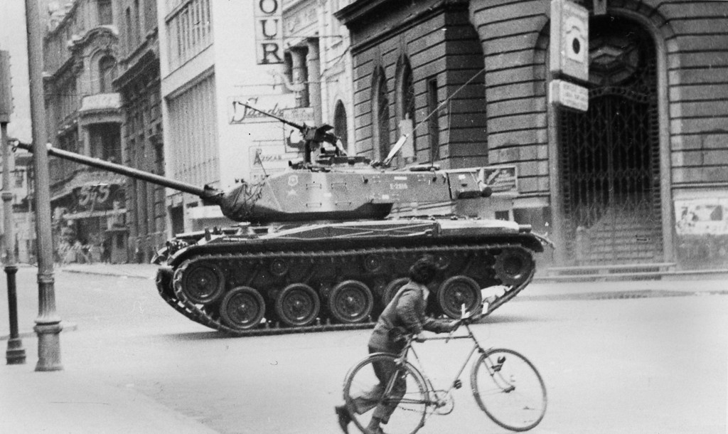 . In this Sept. 11, 1973 file photo, a boy pushes a bicycle across a deserted street as an army tank moves towards La Moneda presidential palace during a coup against President Salvador Allende\'s government, after which Gen. Augusto Pinochet seized power, in Santiago, Chile. On Wednesday, Sept. 11, 2013, Chile marks the 40th anniversary of the coup. (AP Photo/File)