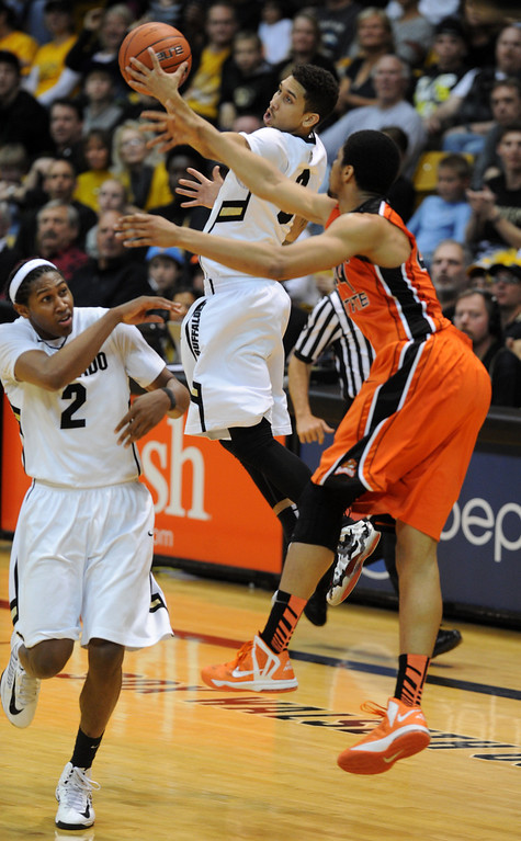 . Askia Booker of Colorado goes up to get a pass as Devon Collier of Oregon State, right, defends during the second half of the March 9, 2013 game in Boulder. Xavier Johnson of Colorado is on the left.    (Cliff Grassmick/Boulder Daily Camera)