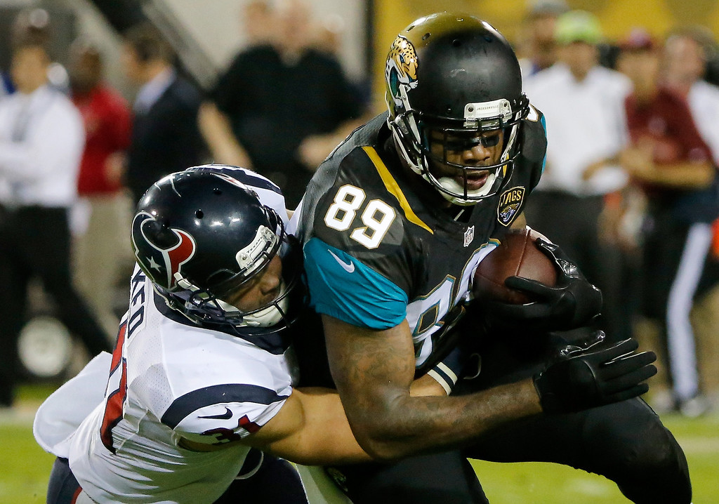 . Marcedes Lewis #89 of the Jacksonville Jaguars is tackled by  Darryl Sharpton #51 of the Houston Texans during the game at EverBank Field on December 5, 2013 in Jacksonville, Florida.  (Photo by Sam Greenwood/Getty Images)