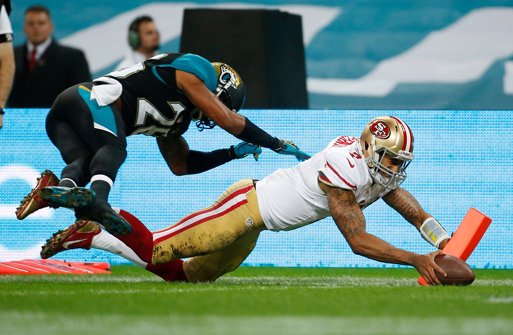 . San Francisco 49ers quarterback Colin Kaepernick (7) scores a 12-yard touchdown while being pursued by Jacksonville Jaguars free safety Josh Evans (26) during the NFL football game at Wembley Stadium, London, Sunday, Oct. 27, 2013.  (AP Photo/Matt Dunham)