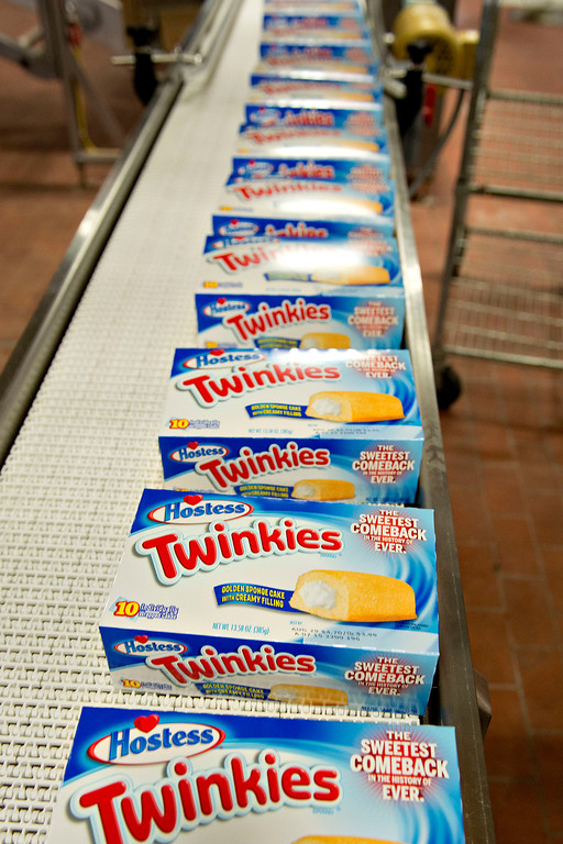 . Boxes of Hostess Brands LLC Twinkies snack cakes travel on a conveyor at the company\'s bakery in Schiller Park, Illinois, U.S., on Monday, July 15, 2013. Photographer: Daniel Acker/Bloomberg