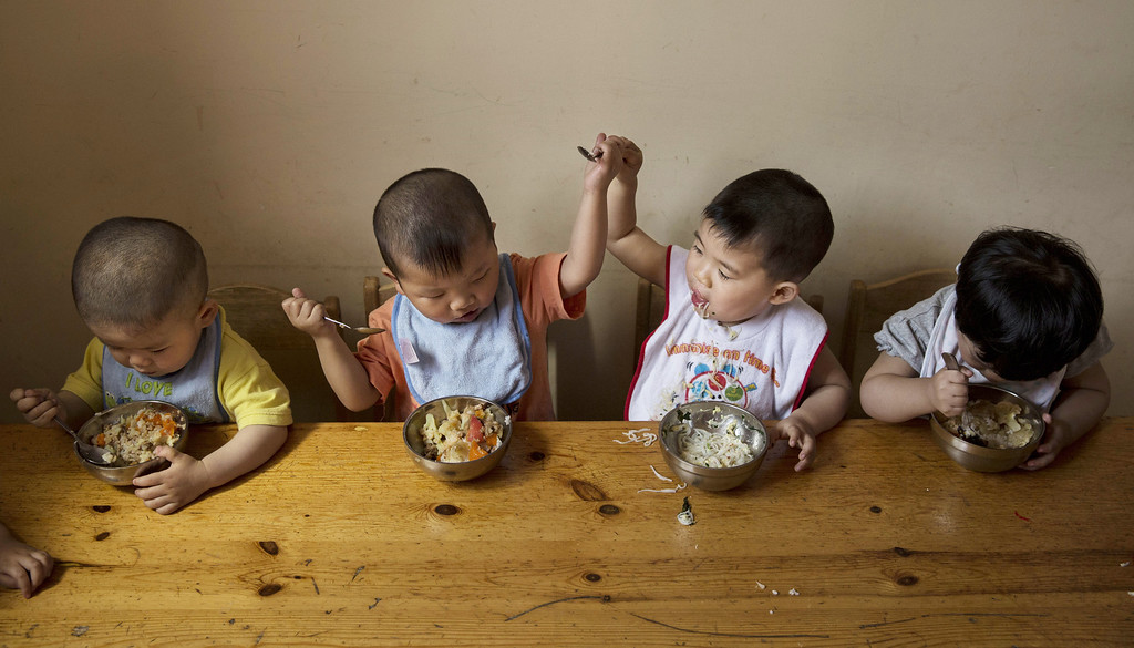 . A young orphaned Chinese boy prevents another from taking some of his food as they eat a meal during feeding at a foster care center on April 2, 2014 in Beijing, China.   (Photo by Kevin Frayer/Getty Images)