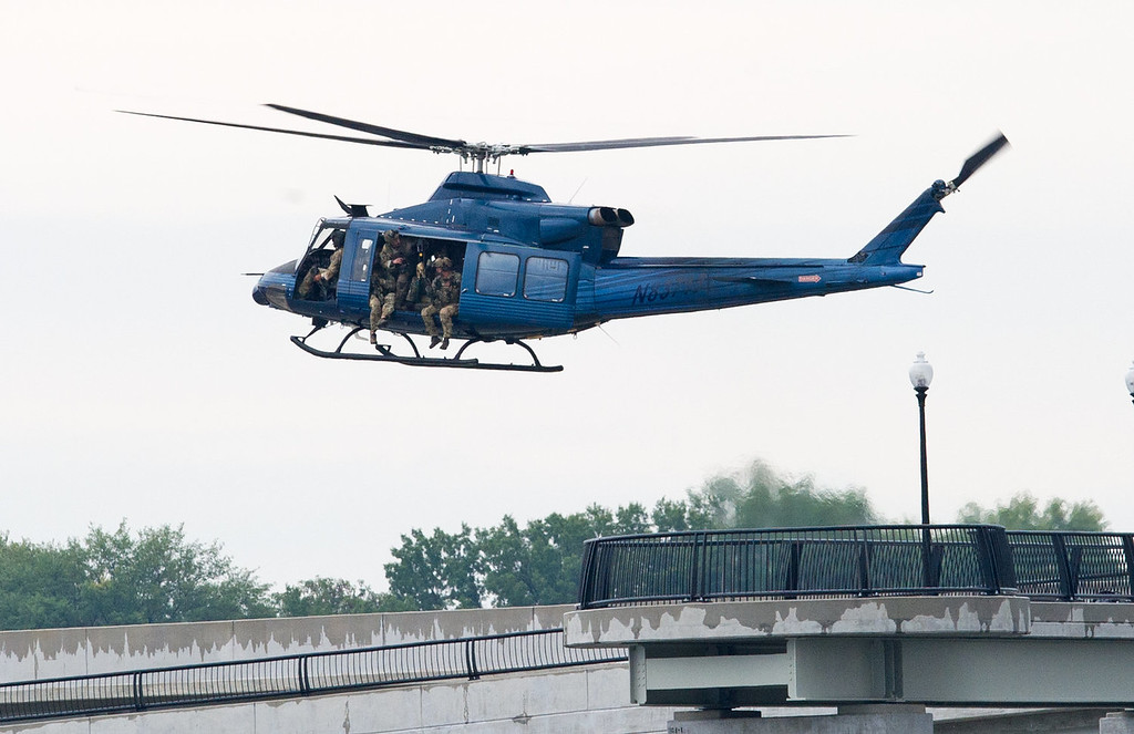 . An unmarked helicopter approaches for a landing on the Route 295 bridge, now a police landing zone, over the Ancostia River near the US Navy Yard on September 16, 2013 in Washington,DC.  An unidentified gunman opened fire at the US Navy Yard in Washington on Monday and wounded several people including two police officers, officials reported. Police and FBI agents descended on the area in force as helicopters buzzed overhead, amid reports the shooter was armed with an assault rifle and was on the loose in the complex. A Washington DC police officer and another law enforcement officer had been shot while the gunman had allegedly barricaded himself in a room in a headquarters building, the Washington Post and other media reported. At one point a police helicopter hovering over the complex lowered a man down by rope into the compound. Police blocked off intersections around the Navy Yard as military troops in uniform stood guard at street corners.   PAUL J. RICHARDS/AFP/Getty Images