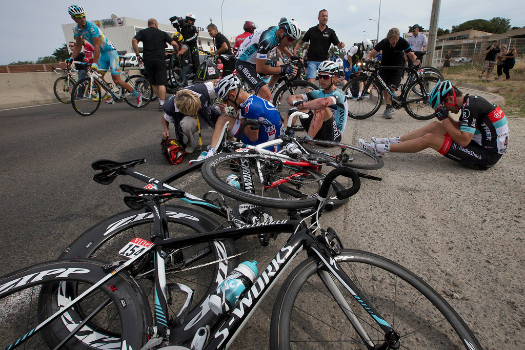 . Murilo Antoniobil Fischer of Brazil, center left, Tony Martin of Germany, center right, and Tony Gallopin of France, right, wait for medical assistance after crashing in the last kilometers of the first stage of the Tour de France cycling race over 213 kilometers (133 miles) with start in Porto Vecchio and finish in Bastia, Corsica island, France, Saturday June 29, 2013. (AP Photo/Joel Saget, POOL)