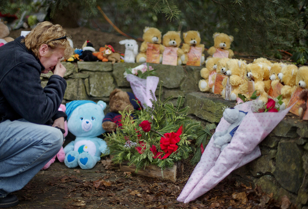 . Cheryl Girardi, of Middletown, Conn., kneels beside 26 teddy bears, each representing a victim of the Sandy Hook Elementary School shooting, at a sidewalk memorial, Sunday, Dec. 16, 2012, in Newtown, Conn. A gunman walked into Sandy Hook Elementary School in Newtown Friday and opened fire, killing 26 people, including 20 children.(AP Photo/David Goldman)