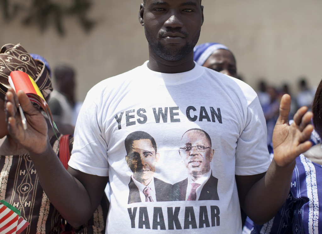 ". A man wearing a t-shirt with the images of President Barack Obama and Senegalese President Macky Sall that says ""Yes We Can Yaakaar\"", yaakaar meaning hope, stands outside the all-girls Martin Luther King Middle School during a visit by first lady Michelle Obama and Senegal\'s first lady Mariame Faye Sall, Thursday, June 27, 2013, in Dakar, Senegal. (AP Photo/Carolyn Kaster)"