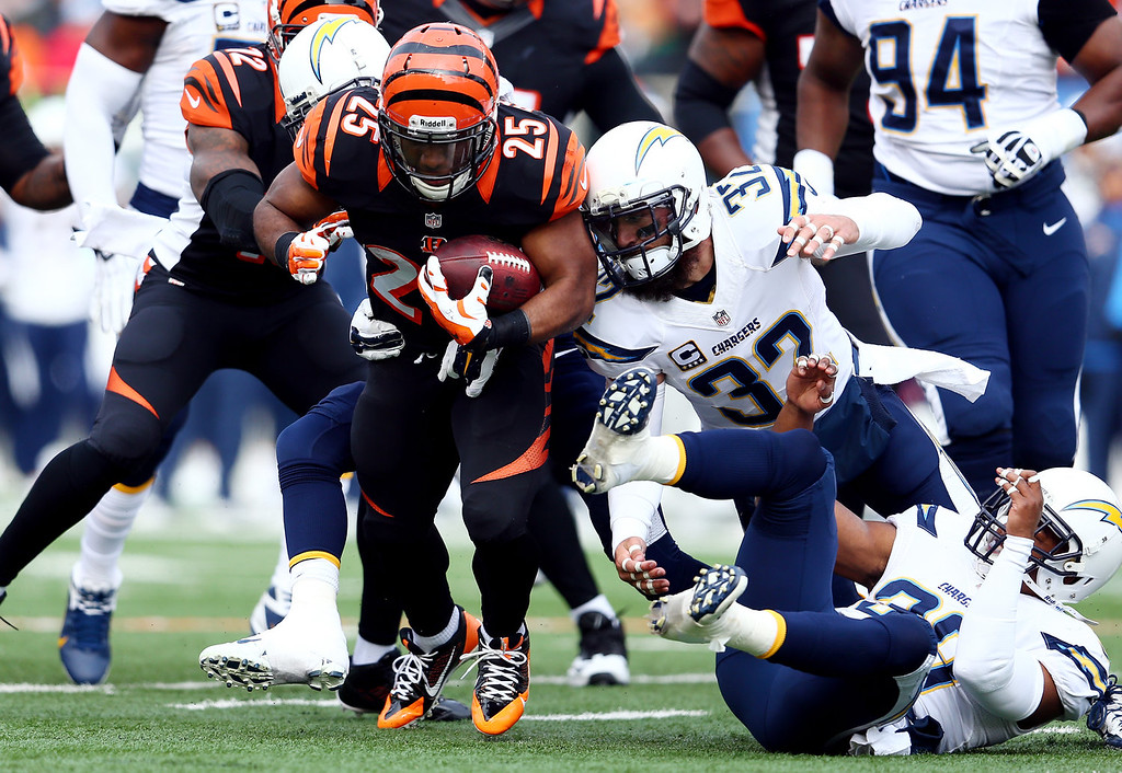 . Running back Gio Bernard #25 of the Cincinnati Bengals carries the ball as free safety Eric Weddle #32 of the San Diego Chargers defends during a Wild Card Playoff game at Paul Brown Stadium on January 5, 2014 in Cincinnati, Ohio.  (Photo by Andy Lyons/Getty Images)