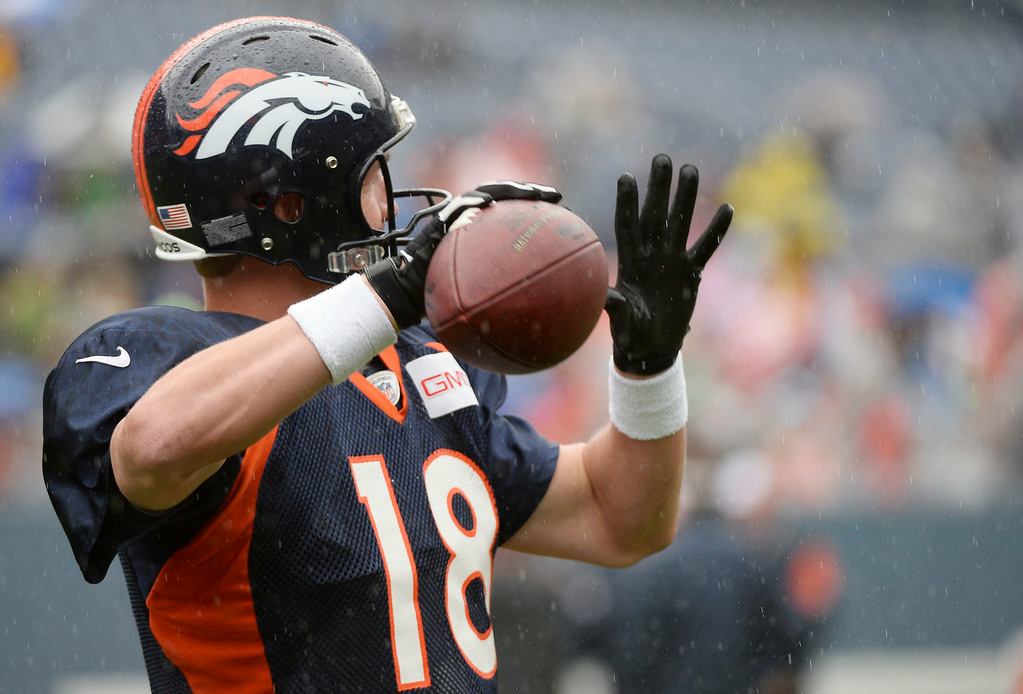 . Denver Broncos quarterback Peyton Manning (18) throws a pass as he wears the glove during a rain day on day six of the Denver Broncos 2014 training camp July 30, 2014 at Sports Authority Field at Mile High Stadium.  (Photo by John Leyba/The Denver Post)