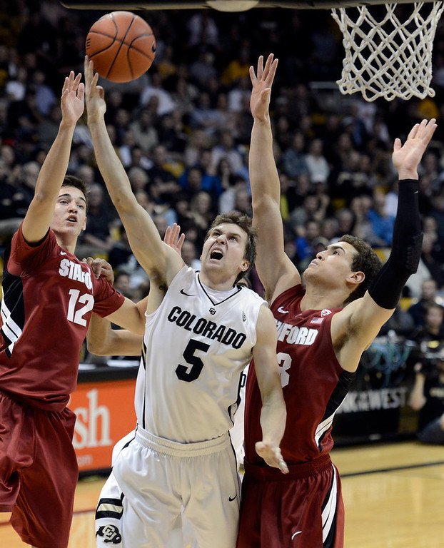 . University of Colorado\'s Eli Stalzer takes a shot over Rosco Allen, No. 12, and Dwight Powell, at right, during a game against Stanford on Thursday, Jan. 24, at the Coors Event Center on the CU campus in Boulder. Jeremy Papasso/ Camera