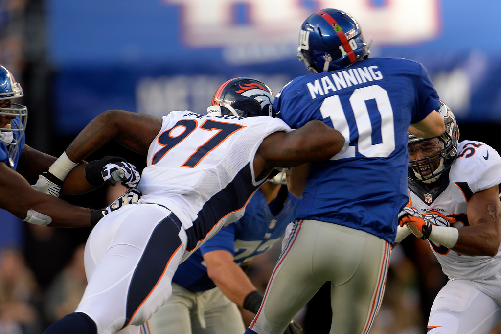 . Defensive end Malik Jackson (97) of the Denver Broncos puts a huge hit on quarterback Eli Manning (10) of the New York Giants as he releases the ball on third down at METLIFE Stadium. The pass was incomplete September 15, 2013 East Rutherford, NJ. (Photo By Joe Amon/The Denver Post)