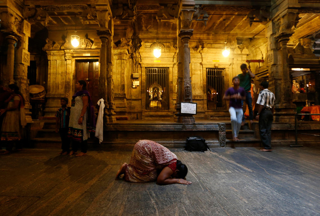 . A Sri Lankan ethnic Tamil Hindu devotee prostrates in prayer during the Hindu festival of lights \'Diwali\' at a temple in Colombo, Sri Lanka, Saturday, Nov. 2, 2013. Hindus light up their homes and pray to Lakshmi, the goddess of wealth, during Diwali festival. (AP Photo/Eranga Jayawardena)