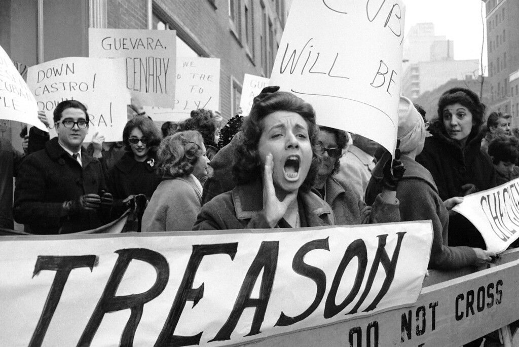 . A woman, standing over a ìTreasonî poster, screams at Ernesto ìCheî Guevara as the aide to Cuban Premier Fidel Castro arrives at a CBS-TV studio in New York on Dec. 13, 1964 to appear on a news interview program. Police held more than 150 demonstrators behind barricades during Guevaraís arrival. (AP Photo)