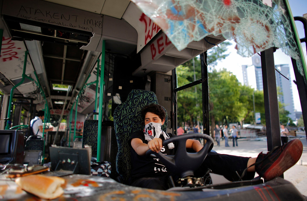 . A Besiktas soccer fan uses his team\'s scarf as a mask while sitting in a damaged bus at Taksim Square in central Istanbul June 4, 2013.  To match TURKEY-PROTESTS/SOCCER REUTERS/Murad Sezer