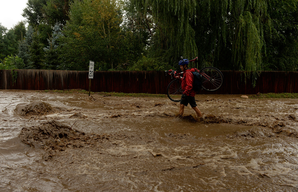 . BOULDER, CO - SEPTEMBER 12: Brady Robinson gives up on trying to ride his bike down Topaz Dr. in north Boulder, September 12, 2013. Massive flash flooding is on going along the Front Range of Colorado. (Photo By RJ Sangosti/The Denver Post)