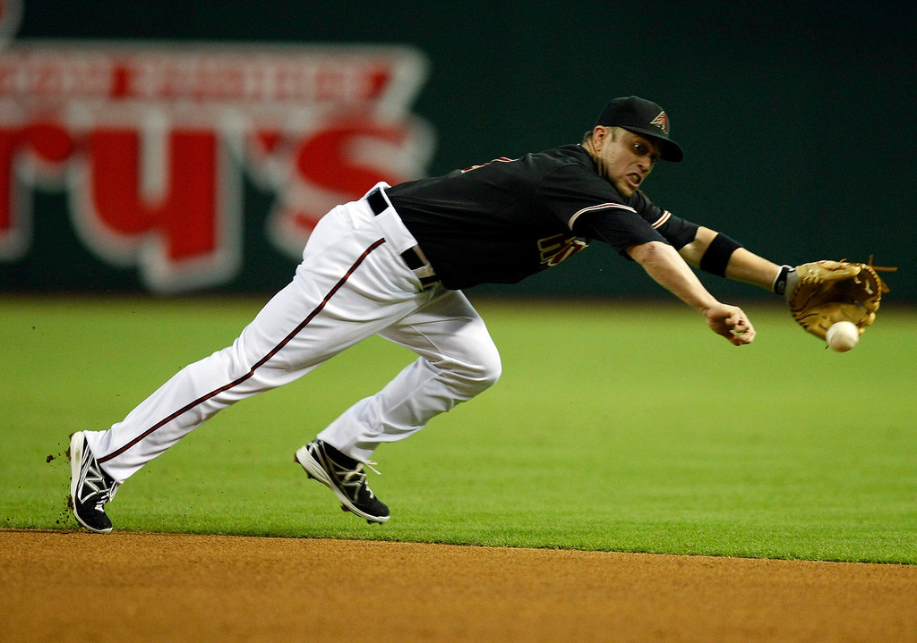 . Arizona Diamondbacks second baseman Aaron Hill  dives for the ball in the first inning during a baseball game against the Colorado Rockies on Sunday, July 7, 2013, in Phoenix. (AP Photo/Rick Scuteri)