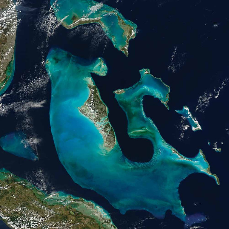 . Grand Bahama Bank, Atlantic Ocean Near Florida and Cuba, the underwater terrain is hilly and the crests of many of these hills compose the islands of the Bahamas. A striking feature of this 2009 Aqua image is the Great Bahama Bank, a massive underwater hill underlying Andros Island in the west, Eleuthera Island in the east, and multiple islands in between. To the north, another bank underlies a set of islands, including Grand Bahama. The varied colors of these banks suggest that their surfaces are somewhat uneven. The banks� distinct contours, sharply outlined in dark blue, indicate that the ocean floor drops dramatically around them. Over the banks, the water depth is often less than 10 meters, but the surrounding basin plunges to depths as low as 4,000 meters.   NASA