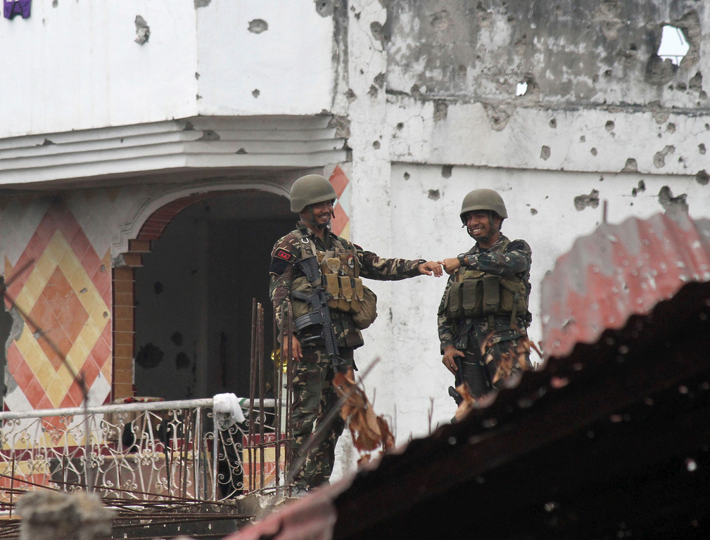 . Government troopers bump fists at the site of a three-week intense fighting between Government forces and Muslim rebels who have taken nearly 200 people hostages, in Zamboanga city, southern Philippines, Saturday Sept. 28, 2013. The deadly standoff ended with all of the captives safe, officials said Saturday. Defense Secretary Voltaire Gazmin said only a handful of Moro National Liberation Front rebels remained in hiding and were being hunted by troops in the coastal outskirts of the city, adding authorities were trying to determine if rebel commander Habier Malik, who led the Sept. 9 siege, was dead. More than 200 people were killed in the clashes, including 183 rebels and 23 soldiers and police, in one of the bloodiest and longest-running attacks by a Muslim group in the south, scene of decades-long Muslim rebellion for self-rule in the largely Roman Catholic country. (AP Photo)
