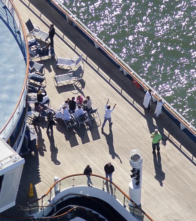 . Passengers congregate on an upper deck of the disabled Carnival Lines cruise ship Triumph as it is towed to harbor off Mobile Bay, Ala., Thursday, Feb. 14, 2013 (AP Photo/Gerald Herbert)