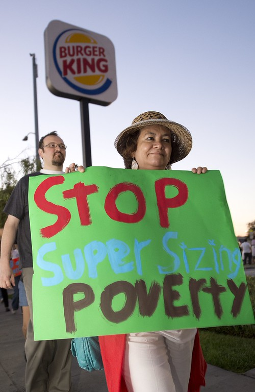 ". A sign reading ""Stop Super Sizing Poverty\"" is carried as fast food workers and their supporters picket outside a Burger King restaurant in Los Angeles on August 29, 2013.   AFP PHOTO / Robyn BECK/AFP/Getty Images"