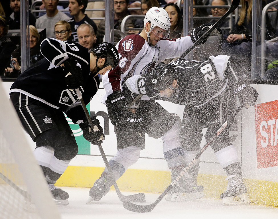 . Colorado Avalanche\'s Paul Stastny, center, fights for the puck with Los Angeles Kings\' Jarret Stoll, right, and Kyle Clifford during the second period of an NHL hockey game on Saturday, Nov. 23, 2013, in Los Angeles.(AP Photo/Jae C. Hong)