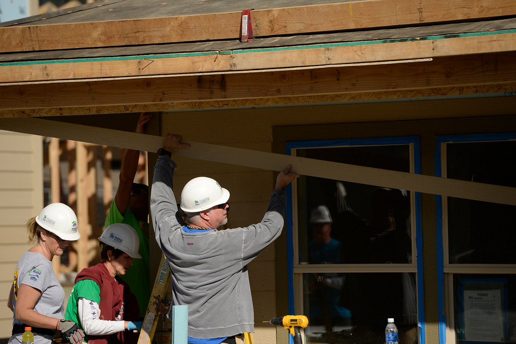 . DENVER, CO - OCTOBER 09: Garth Brooks puts on siding during Habitat for Humanity\'s Carter Work Project event in the Globeville Neighborhood in Denver, October 09, 2013. The Humanity\'s Carter Work Project will complete 11 new townhouses. (Photo By RJ Sangosti/The Denver Post)
