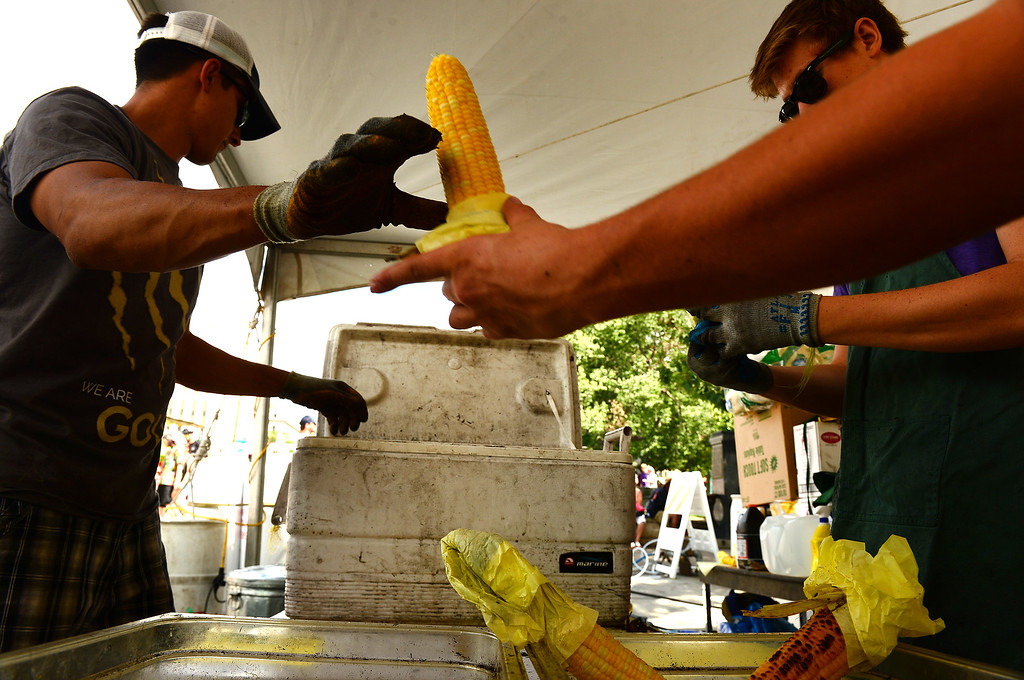 . Jordan Alvarez, left and Craig Tietbohl, right, with the Colorado Corn Company, shuck corn as fast as they can to feed hungry fair-goers at  the Taste of Colorado at Civic Center Park in Denver on August 31, 2014.  The corn on the cob stand estimates that they go through a case of corn every 10 minutes during the festival.  There are 48 pieces of corn in a case. The corn, which comes from Sakata Farms in Brighton, is cooked at 550 degrees for 22 minutes and soaked in warm butter making for a very popular food item at the festival.  (Photo By Helen H. Richardson/ The Denver Post)
