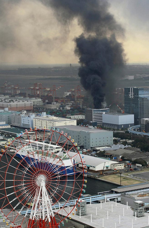 . Black smoke rises from a burning building in Tokyo after Japan was struck by a magnitude 8.9 earthquake off its northeastern coast Friday, March 11, 2011. (AP Photo/Kyodo News)