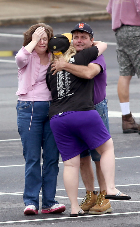 . A FedEx employee, right, is consoled as other FedEx employees wait to meet their family at a nearby business after they were evacuated from the Airport Road FedEx facility after an early morning shooting Tuesday April 29, 2014, in Kennesaw, Ga. (AP Photo/Jason Getz)