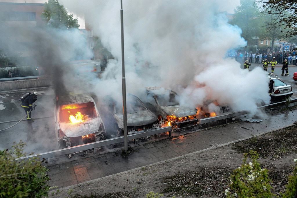. Firemen extinguish a row of burning cars in the Stockholm suburb of Rinkeby after youths rioted in several different suburbs around Stockholm for a fourth consecutive night, late May 23, 2013. Youths in immigrant-heavy Stockholm suburbs torched cars and threw rocks at police in riots believed to be linked to a deadly police shooting of a local resident in the suburb of Husby. (AP Photo/Scanpix, Fredrik Sandberg)