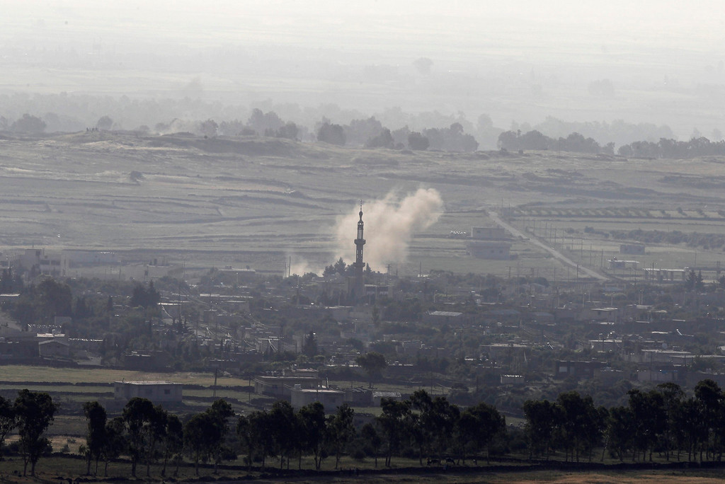 . Smoke rises after shells exploded in the Syrian village of Al Rafeed, close to the ceasefire line between Israel and Syria, as seen from the Israeli occupied Golan Heights May 7, 2013. Israel played down weekend air strikes close to Damascus reported to have killed dozens of Syrian soldiers, saying they were not aimed at influencing its neighbour\'s civil war but only at stopping Iranian missiles reaching Lebanese Hezbollah militants. REUTERS/Baz Ratner