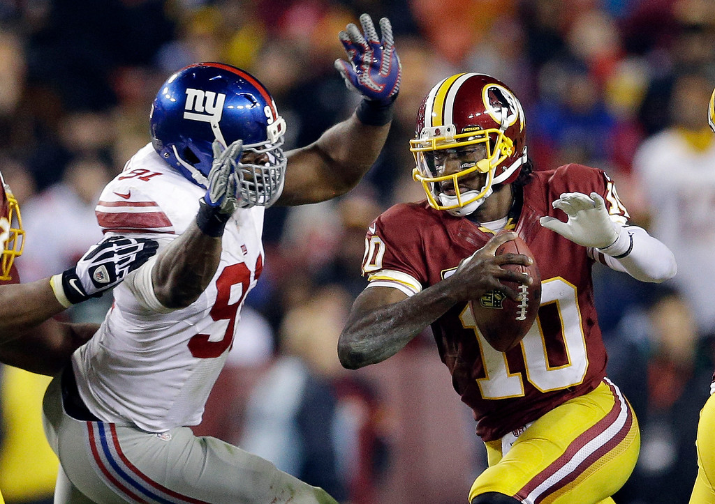 . New York Giants defensive end Justin Tuck, left, tackles Washington Redskins quarterback Robert Griffin III (10) during the second half of an NFL football game Sunday, Dec. 1, 2013, in Landover, Md. (AP Photo/Patrick Semansky)