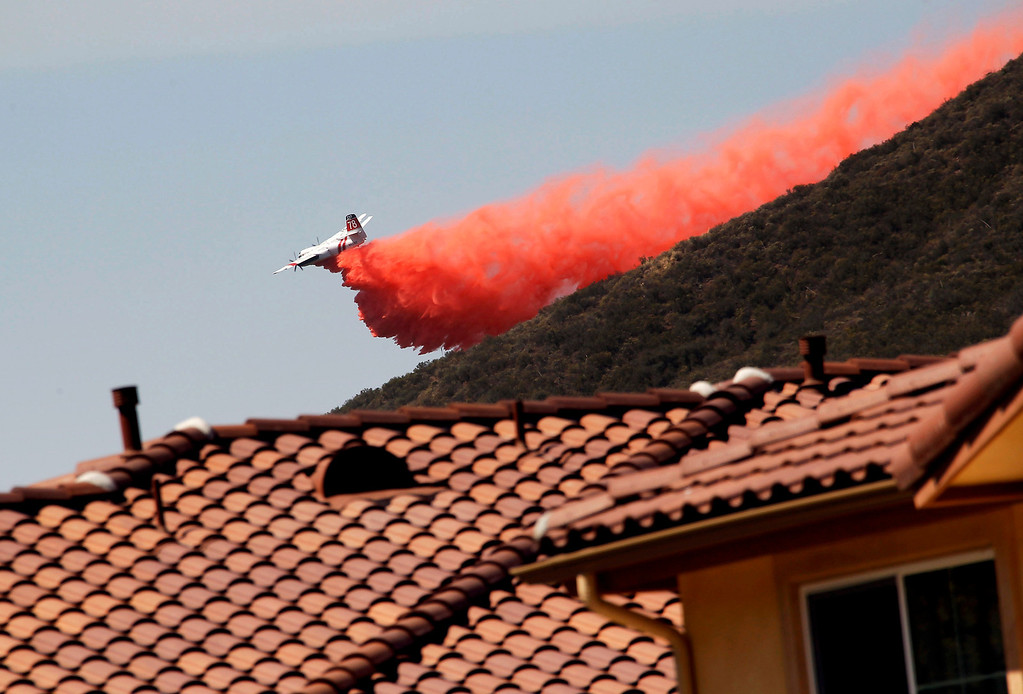 . A firefighting aircraft drops fire retardant along a hill side near homes in Thousand Oaks, Calif. on Thursday, May 2, 2013.  A wildfire fanned by gusty Santa Ana winds raged along the fringes of Southern California communities on Thursday, forcing evacuation of homes and a university while setting recreational vehicles ablaze.  (AP Photo/Nick Ut)