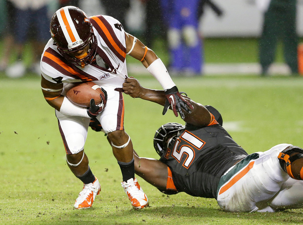 . Virginia Tech running back J.C. Coleman (4) is taken down by Miami defensive lineman Shayon Green (51) during the first half of an NCAA college football game, Saturday, Nov. 9, 2013, in Miami Gardens, Fla. (AP Photo/Wilfredo Lee)
