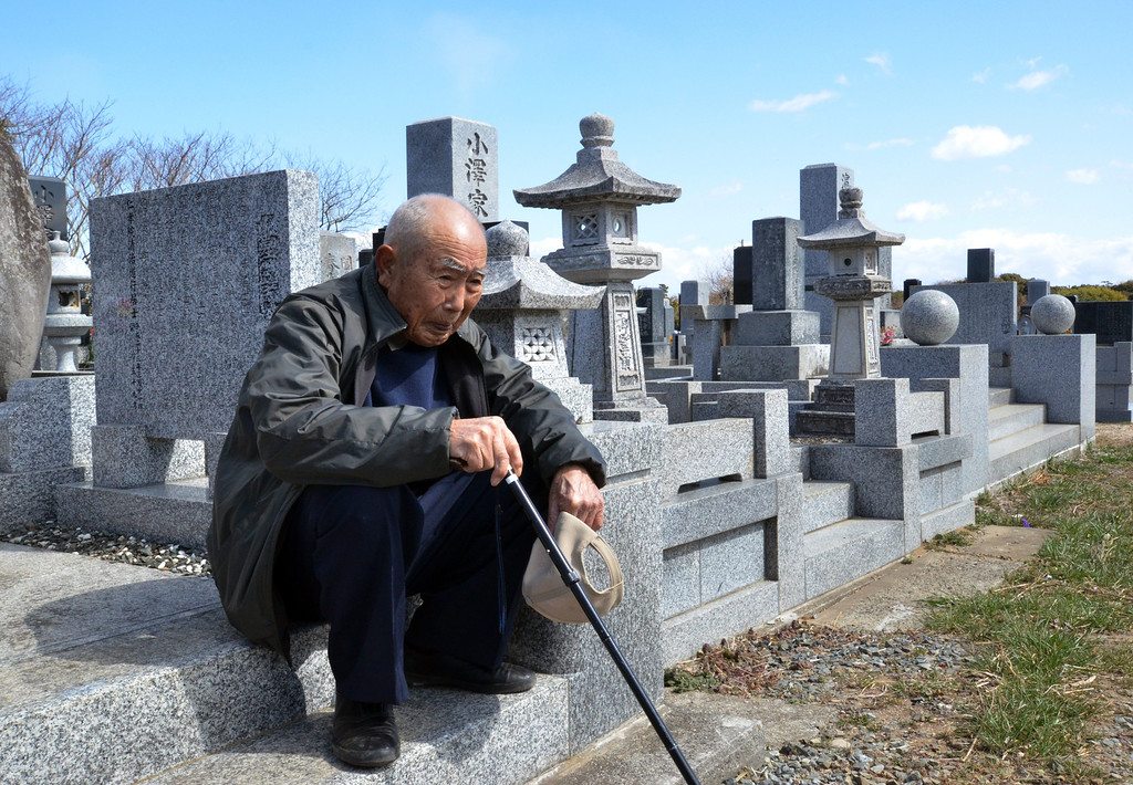 . An elderly man sits as he and with his wife (not pictured) visit a cemetery to pay respects to their son who was killed in the March 2011 tsunami, in Minamisoma in Fukushima prefecture on March 11, 2013. March 11, 2013 marks the second anniversary of the 9.0 magnitude earthquake that sent a huge wall of water into the coast of the Tohoku region, splintering whole communities, ruining swathes of prime farmland and killing nearly 19,000 people.         AFP PHOTO / YOSHIKAZU TSUNO/AFP/Getty Images