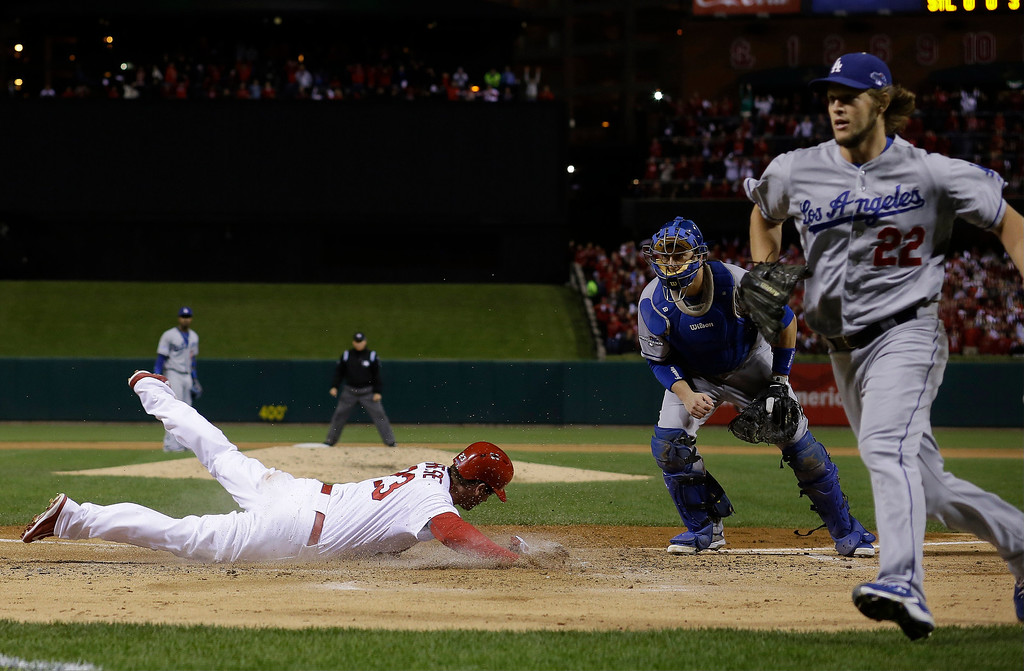 . St. Louis Cardinals\' David Freese scores after a ball got past Los Angeles Dodgers catcher A.J. Ellis during the third inning of Game 6 of the National League baseball championship series, Friday, Oct. 18, 2013, in St. Louis. (AP Photo/David J. Phillip)