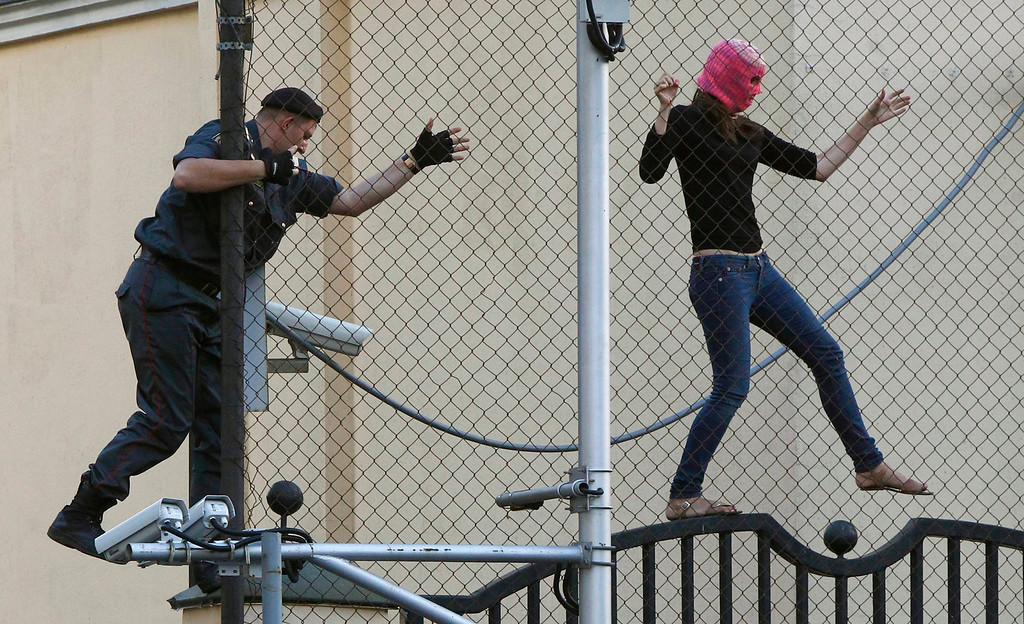 """. A policeman chases a supporter of the female punk band \""""Pussy Riot\"""" jailed members while climbing on a fence enclosing the Turkish embassy near a court building in Moscow, August 17, 2012. Three women from Russian punk band Pussy Riot were sentenced to two years in jail on Friday for their protest against President Vladimir Putin in a church, an outcome supporters described as the Kremlin leader\'s \""""personal revenge\"""". REUTERS/Mikhail Voskresensky"""