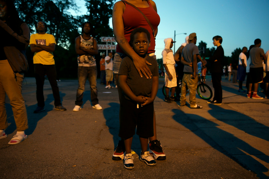 . Jeremiah Parker, 4, stands in front of his mother, Shatara Parker, as they attend a protest Wednesday, Aug. 13, 2014, in Ferguson, Mo. Nights of unrest have vied with calls for calm in a St. Louis suburb where Michael Brown, an unarmed black teenager was killed by police, while the community is still pressing for answers about the weekend shooting. (AP Photo/Jeff Roberson)