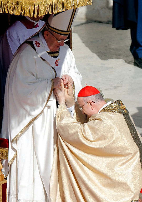 . Pope Francis salutes cardinal Tarcisio Bertone in St. Peter\'s Square at the Vatican, Tuesday, March 19, 2013. Pope Francis urged princes, presidents, sheiks and thousands of ordinary people gathered for his installation Mass on Tuesday to protect the environment, the weakest and the poorest, mapping out a clear focus of his priorities as leader of the world\'s 1.2 billion Catholics. (AP Photo/Dmitry Lovetsky)