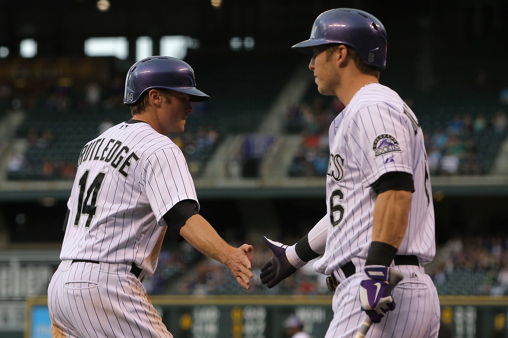 . Josh Rutledge #14 of the Colorado Rockies is welomed home by Corey Dickerson #6 of the Colorado Rockies after scoring on a double by Drew Stubbs #13 of the Colorado Rockies to take a 1-0 lead over the Atlanta Braves in the first inning at Coors Field on June 11, 2014 in Denver, Colorado.  (Photo by Doug Pensinger/Getty Images)