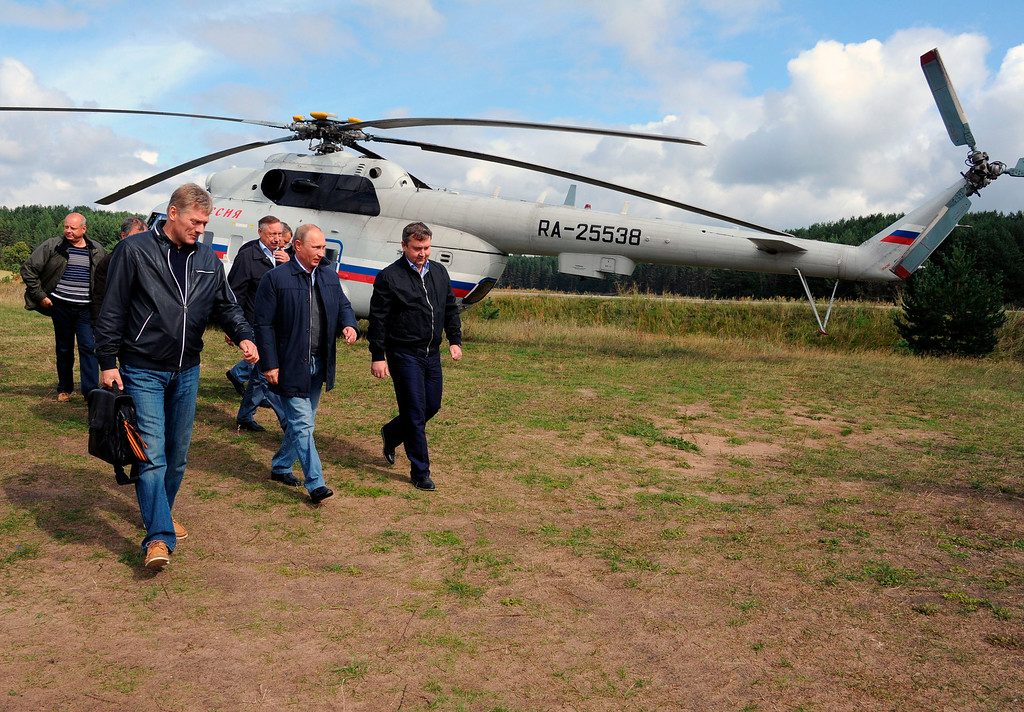 . Russian President Vladimir Putin, center, arrives at a meeting with participants in the youth educational forum at the Seliger youth camp near Lake Seliger, some 450 kilometres (281 miles) northwest of Moscow, in Tver region, Russia, Friday, Aug. 29, 2014. At left is presidential spokesman Dmitry Peskov. (AP Photo/RIA-Novosti, Mikhail Klimentyev, Presidential Press Service)