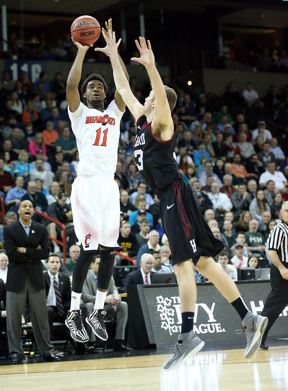 . Jermaine Lawrence #11 of the Cincinnati Bearcats shoots over Evan Cummins #33 of the Harvard Crimson during the second round of the 2014 NCAA Men\'s Basketball Tournament at Spokane Veterans Memorial Arena on March 20, 2014 in Spokane, Washington.  (Photo by Stephen Dunn/Getty Images)