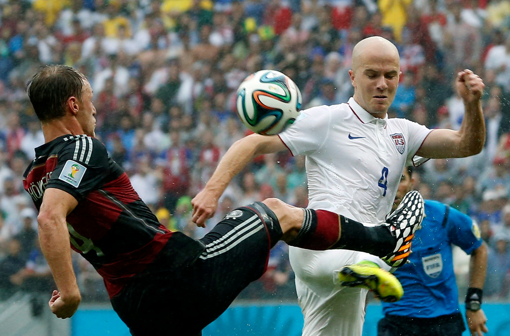 . Germany\'s Benedikt Hoewedes, left, and United States\' Michael Bradley challenge for the ball during the group G World Cup soccer match between the USA and Germany at the Arena Pernambuco in Recife, Brazil, Thursday, June 26, 2014. (AP Photo/Matthias Schrader)