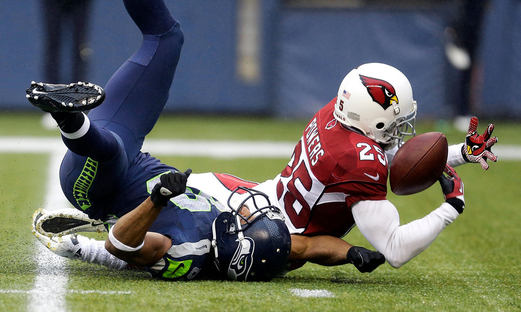 . Arizona Cardinals cornerback Jerraud Powers (25) breaks up a pass intended for Seattle Seahawks wide receiver Doug Baldwin in the second half of an NFL football game, Sunday, Dec. 22, 2013, in Seattle. Powers could not hold on for an interception. (AP Photo/Elaine Thompson)