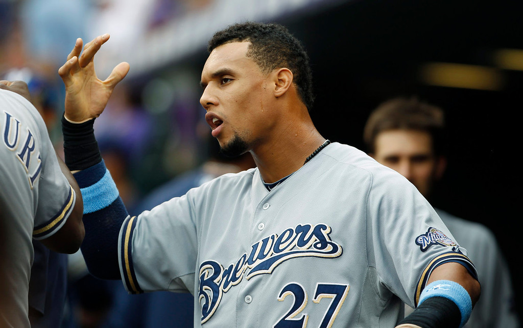 . Milwaukee Brewers center fielder Carlos Gomez jokes with teammates before facing the Colorado Rockies in the first inning of a baseball game in Denver on Sunday, July 28, 2013. (AP Photo/David Zalubowski)