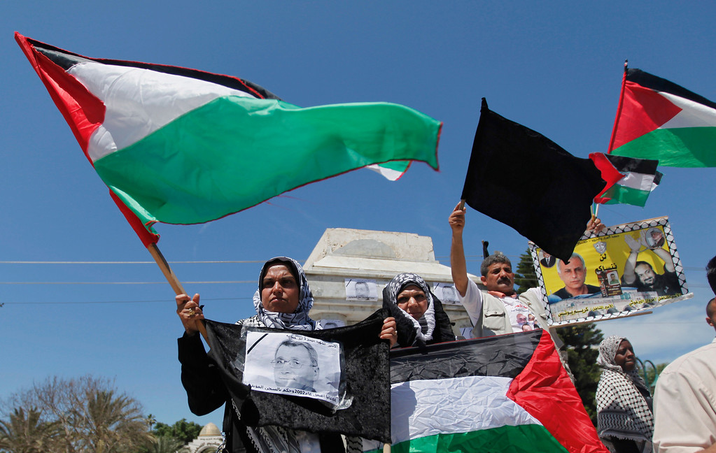 . A Palestinian woman holds a portrait of Maysara Abu Hamdiyeh during a rally in Gaza City, Tuesday, April 2, 2013. Abu Hamdiyeh, 64, who was serving a life sentence for his role in a foiled attempt to bomb a busy cafe in Jerusalem in 2002, died Tuesday of cancer in an Israeli jail. Tensions are high in Israeli lockups where thousands of Palestinian security prisoners are being held. (AP Photo/Hatem Moussa)