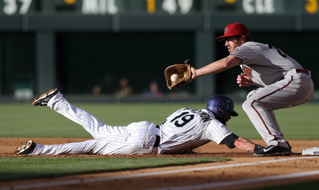 . Arizona Diamondbacks first baseman Nick Evans, right, fields a pickoff throw as Colorado Rockies\' Charlie Blackmon dives back into first base in the first inning of a baseball game in Denver on Tuesday, June 3, 2014. (AP Photo/David Zalubowski)