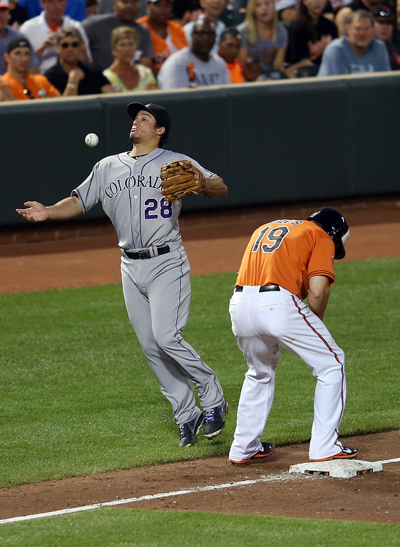 . BALTIMORE, MD - AUGUST 17: Third baseman Nolan Arenado #28 of the Colorado Rockies bobbles a ball hit for an infield single by Adam Jones #10 of the Baltimore Orioles Adam Jones (10) of the Baltimore Orioles (not pictured) in front of Chris Davis #19 during the third inning at Oriole Park at Camden Yards on August 17, 2013 in Baltimore, Maryland.  (Photo by Rob Carr/Getty Images)