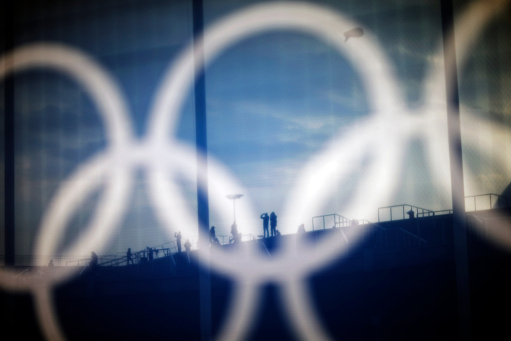 . Spectators are seen through a screen with the Olympic rings on a security fence as they take a photo on the steps of the Bolshoy Ice Dome at the 2014 Winter Olympics, Friday, Feb. 21, 2014, in Sochi, Russia. (AP Photo/David Goldman)