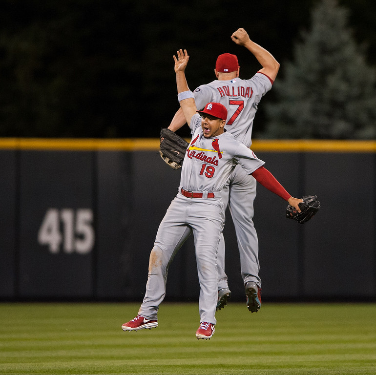 . Jon Jay #19 and Matt Holliday #7 of the St. Louis Cardinals celebrate the win over the Colorado Rockies as they leap in the outfield at Coors Field on September 18, 2013 in Denver, Colorado. (Photo by Dustin Bradford/Getty Images)