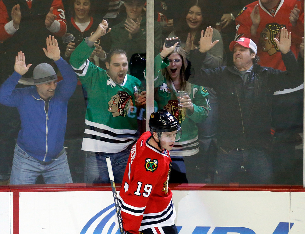 . Fans celebrate the goal of Chicago Blackhawks center Jonathan Toews (19) during the first period of an NHL hockey game against the Colorado Avalanche, Friday, Dec. 27, 2013, in Chicago. (AP Photo/Charles Rex Arbogast)